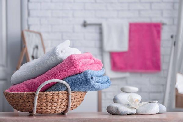 Toalhas lavadas e macias no banheiro dentro de um cesto
