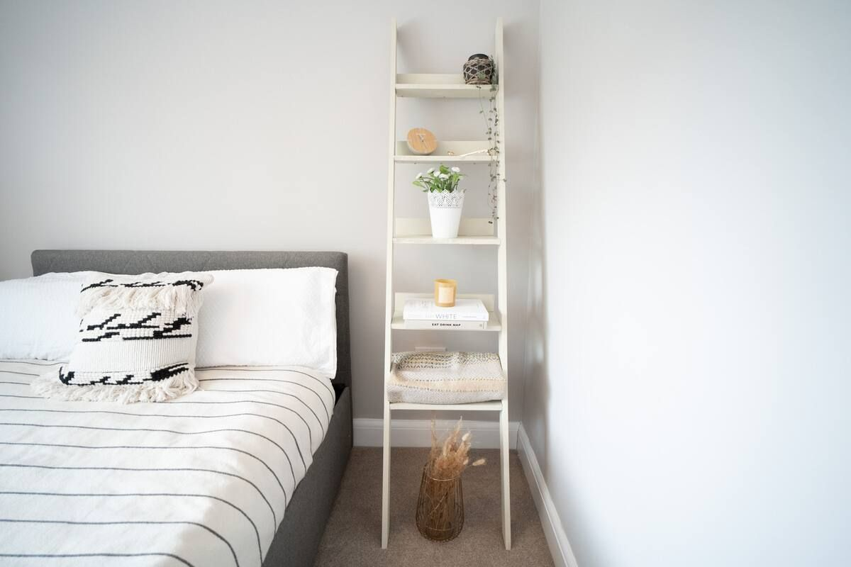 A wooden ladder shelf with various items on it beside a bed in a bedroom