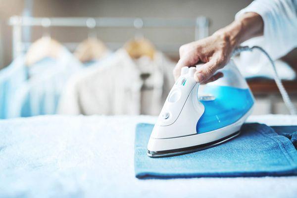 Pessoa utilizando o ferro de passar roupas