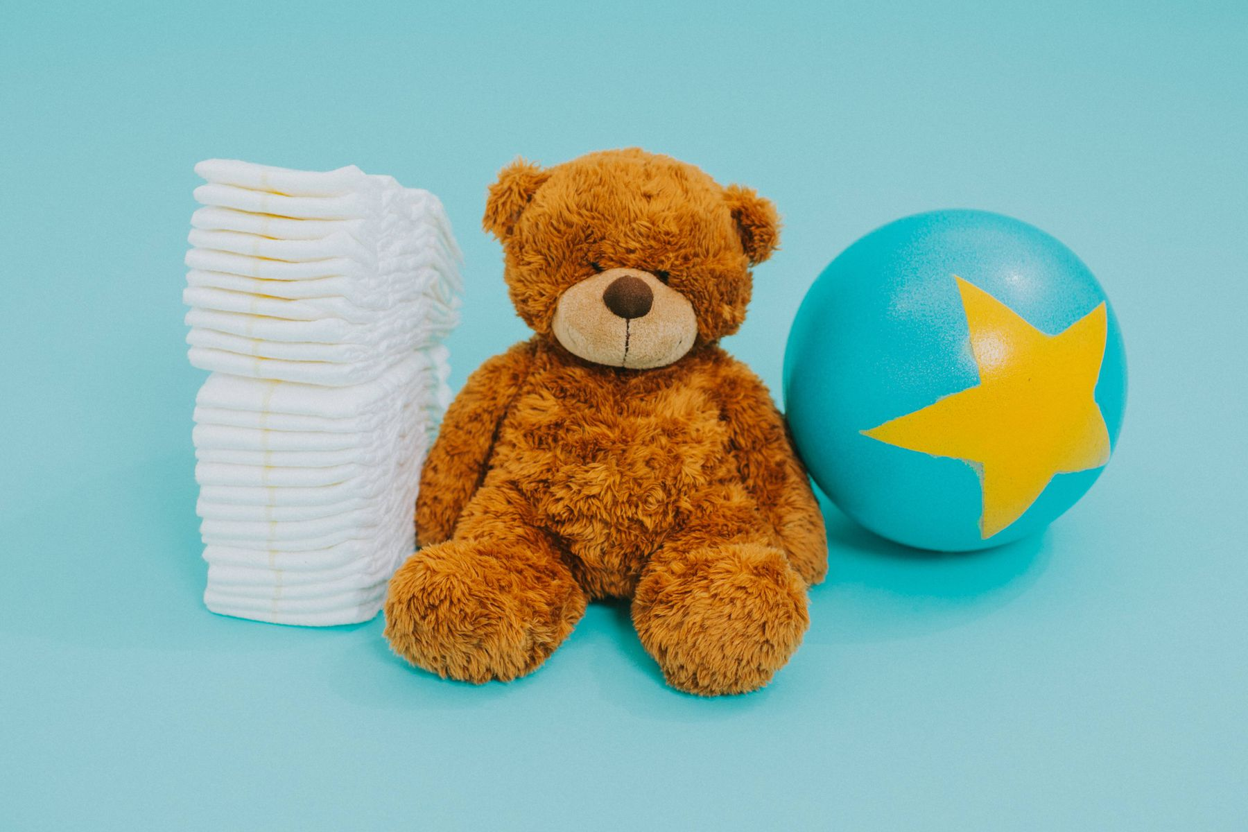 teddy bear sitting around nappies and a plastic ball