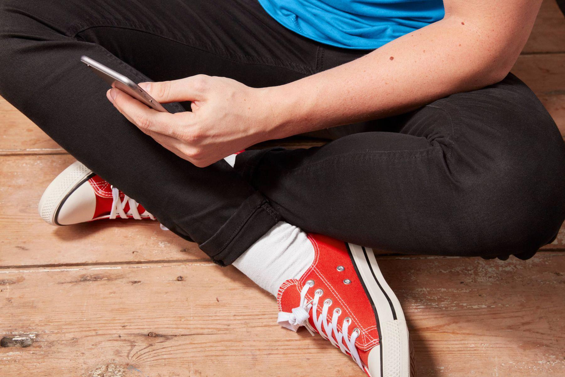 Bağdaş kurmuş, jean pantolonlu ve kırmızı ayakkabılı genç.