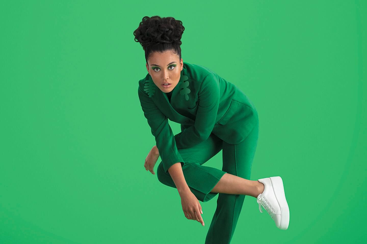 Lady in green suit, white takkies, standing and leaning on knee