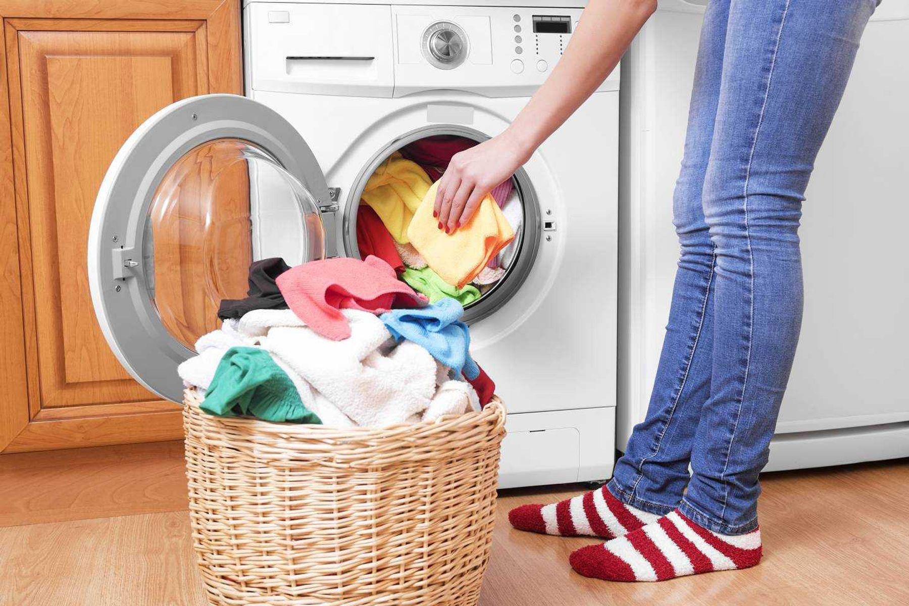 mulher separando roupas coloridas para lavar