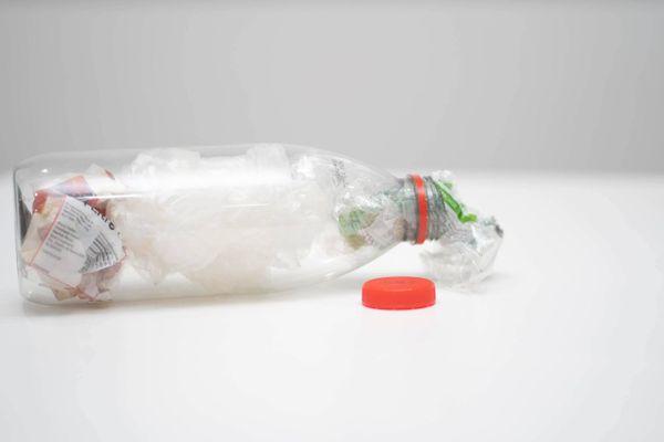 İçi plastik ve kağıt atıklarla dolu yan duran plastik bir şişe