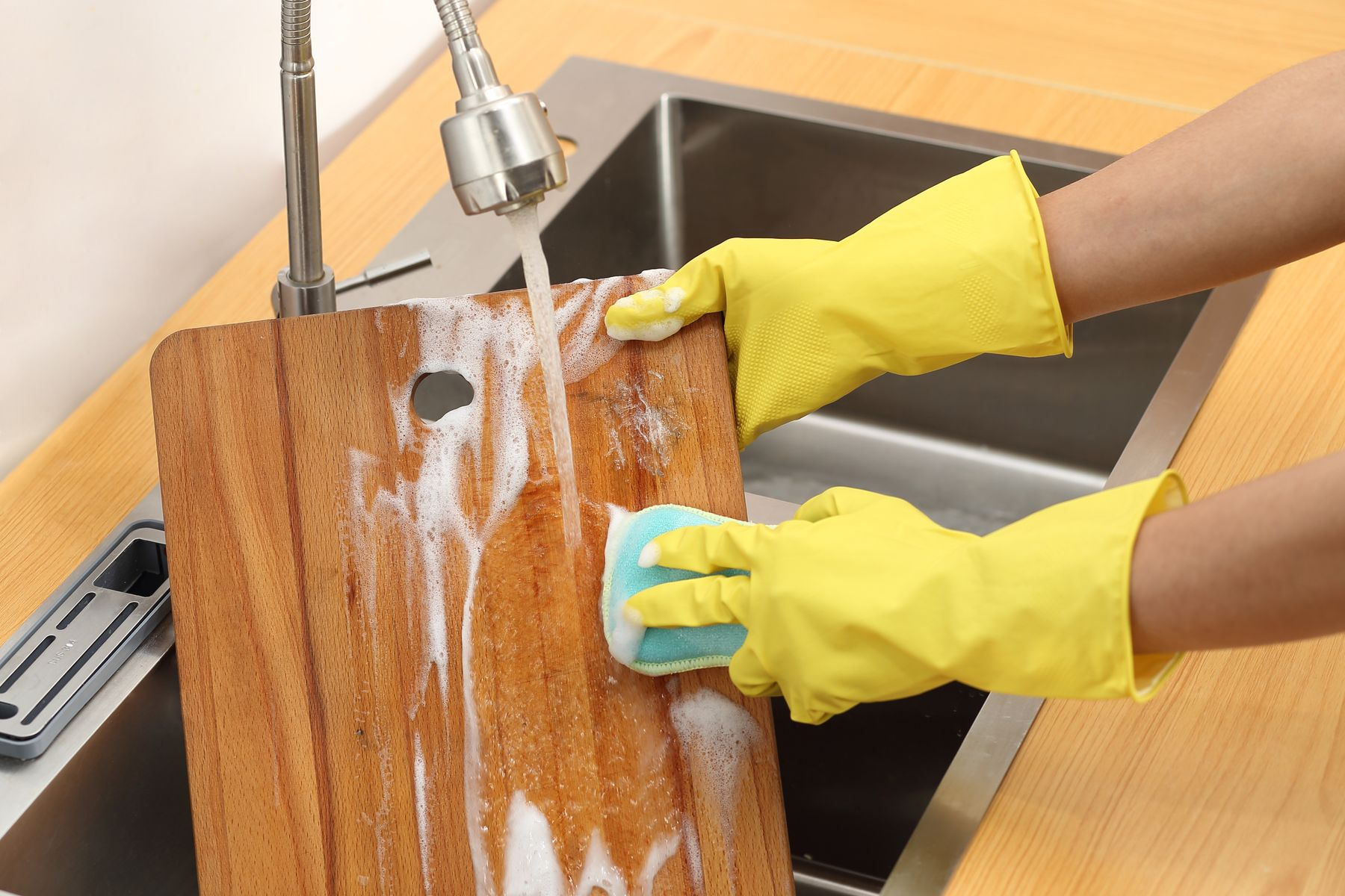 Step 6: Washing a wooden chopping board with hot soapy water in a sink