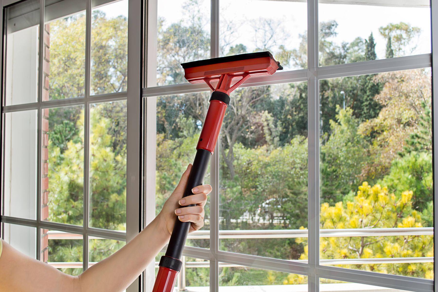 Cam silme lastiği ile temizlik yapan kadın