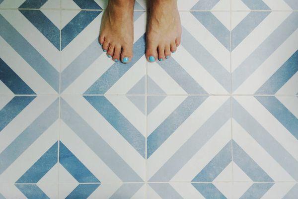 Mavi vintage fayanslar, mavi ojeli kadın ayakları