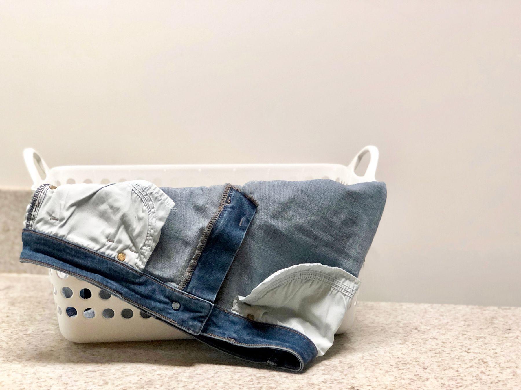 Calça jeans ao avesso dobrada para fora do cesto de roupas