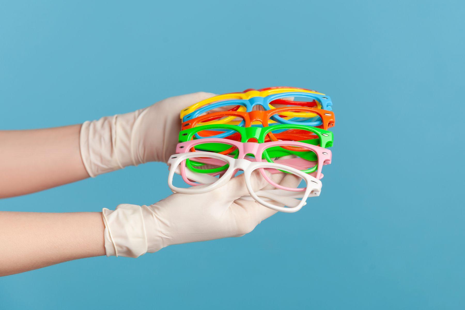 Mão segurando diversos óculos coloridos contra fundo azul