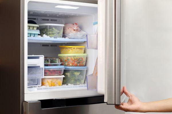 pessoa segurando a porta da geladeira