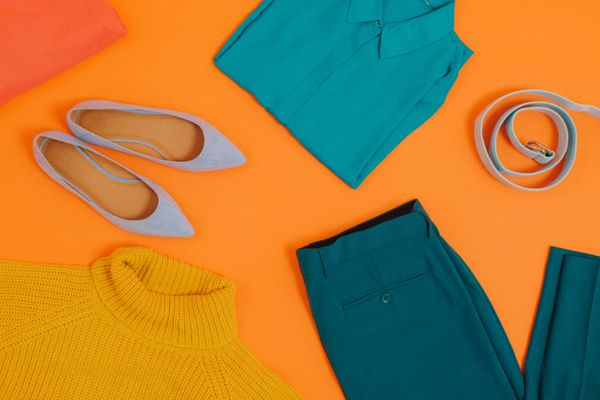 Womens clothes laid against orange backdrop