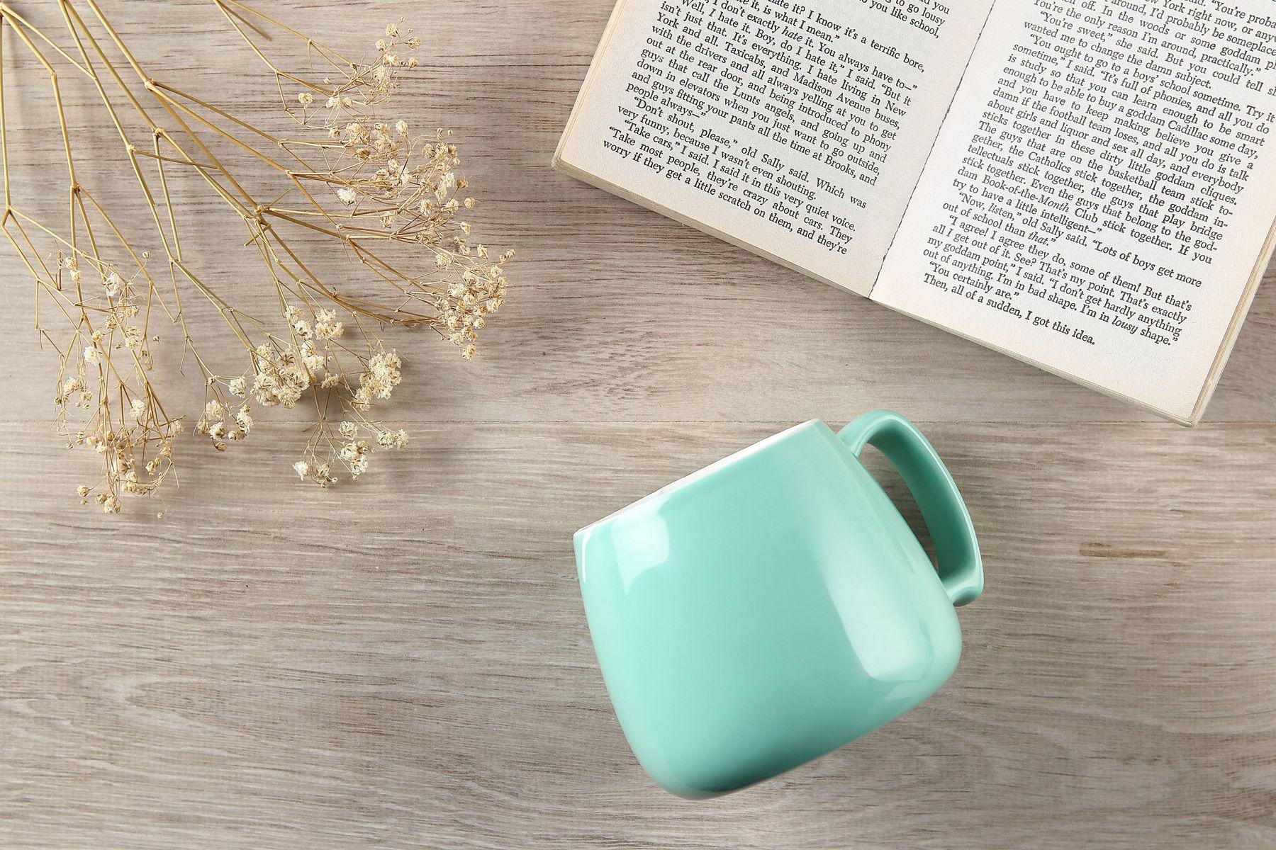 porcelanowy kubek i otwarta książka na drewnianym stole