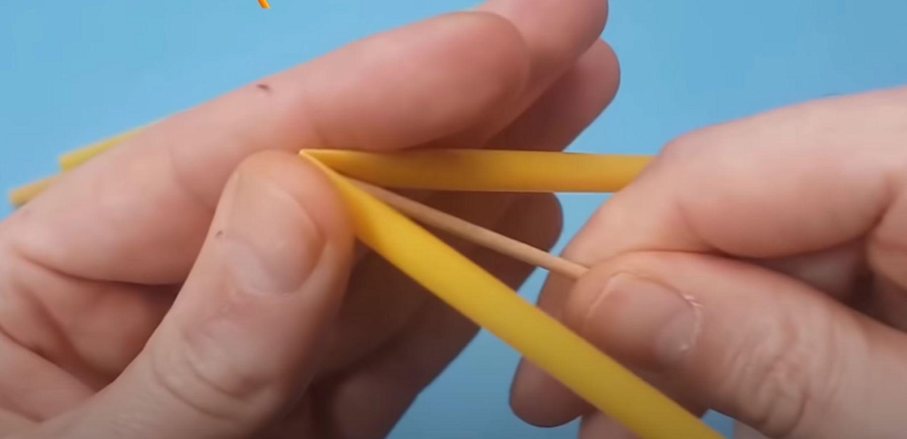Step 3: Dùng tăm đã được gắn với sợi dây xỏ xuyên qua giữa lằn ống hút bị gập