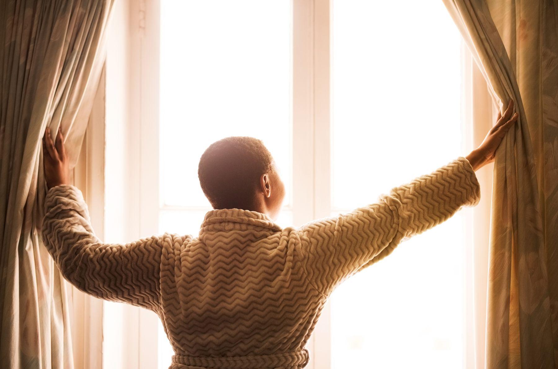 Pessoa abrindo as cortinas da janela