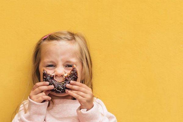 Mädchen vor der gelben Wand lächelnd mit Cookie im Gesicht
