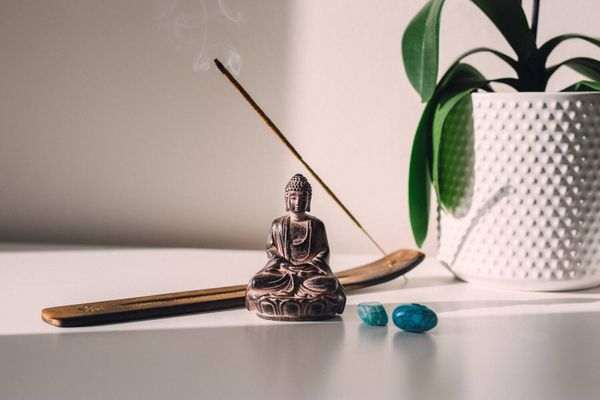 two blue stones, incense and a buddha image next to a plant in a corner of the house