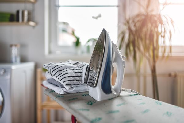 An iron propped up with a pile of t-shirts on the ironing board ready for ironing clothes