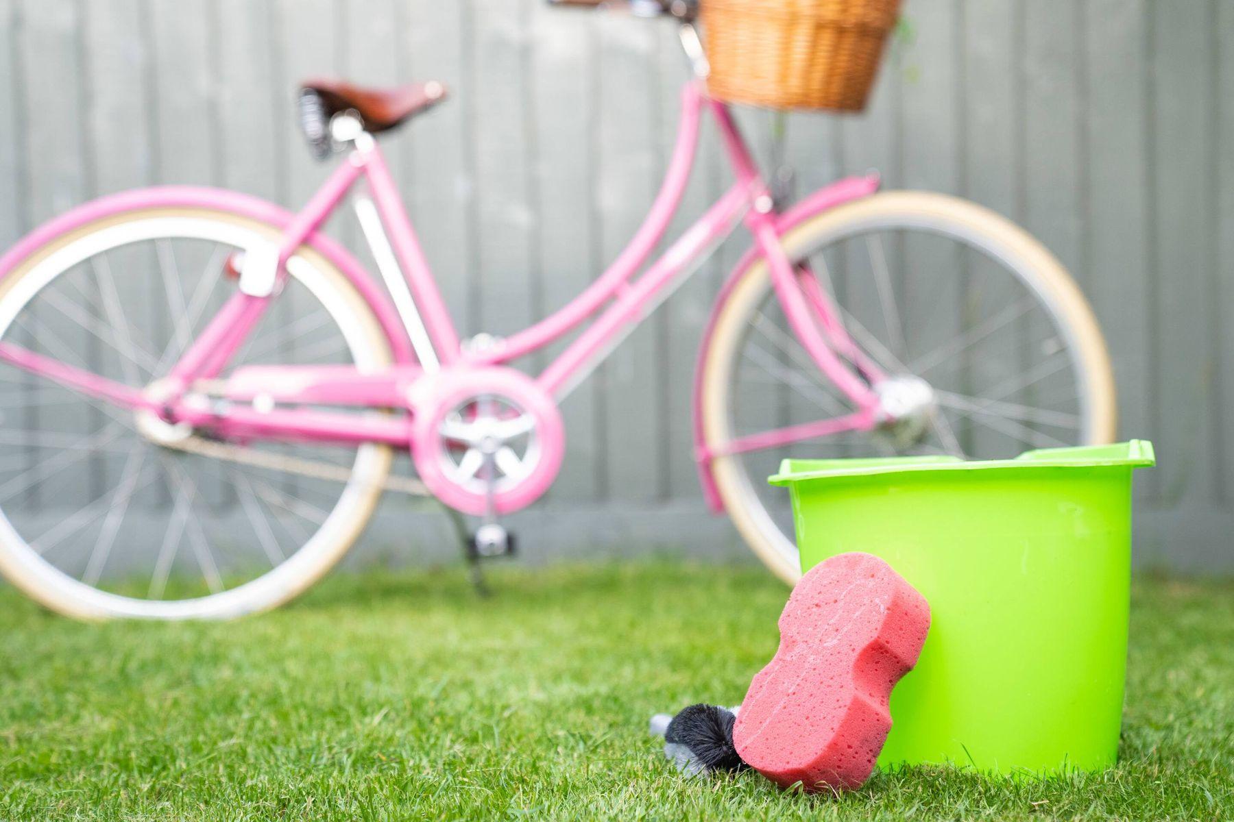 bicicletta rosa in giardino, secchio e panno per la pulizia