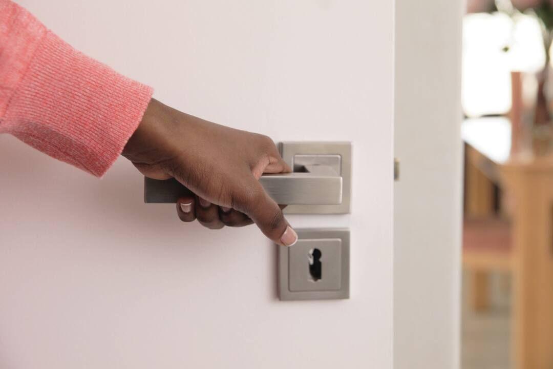 Pessoa fechando porta da casa