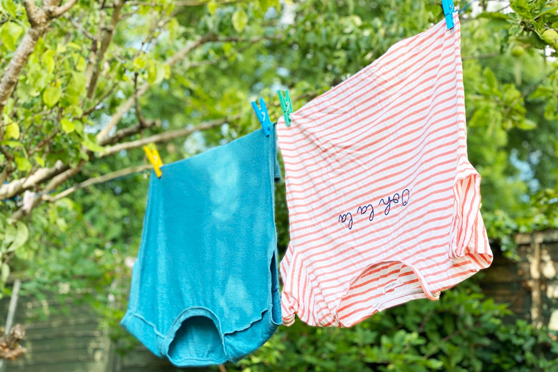 Freshly washed tops drying on a washing line outside