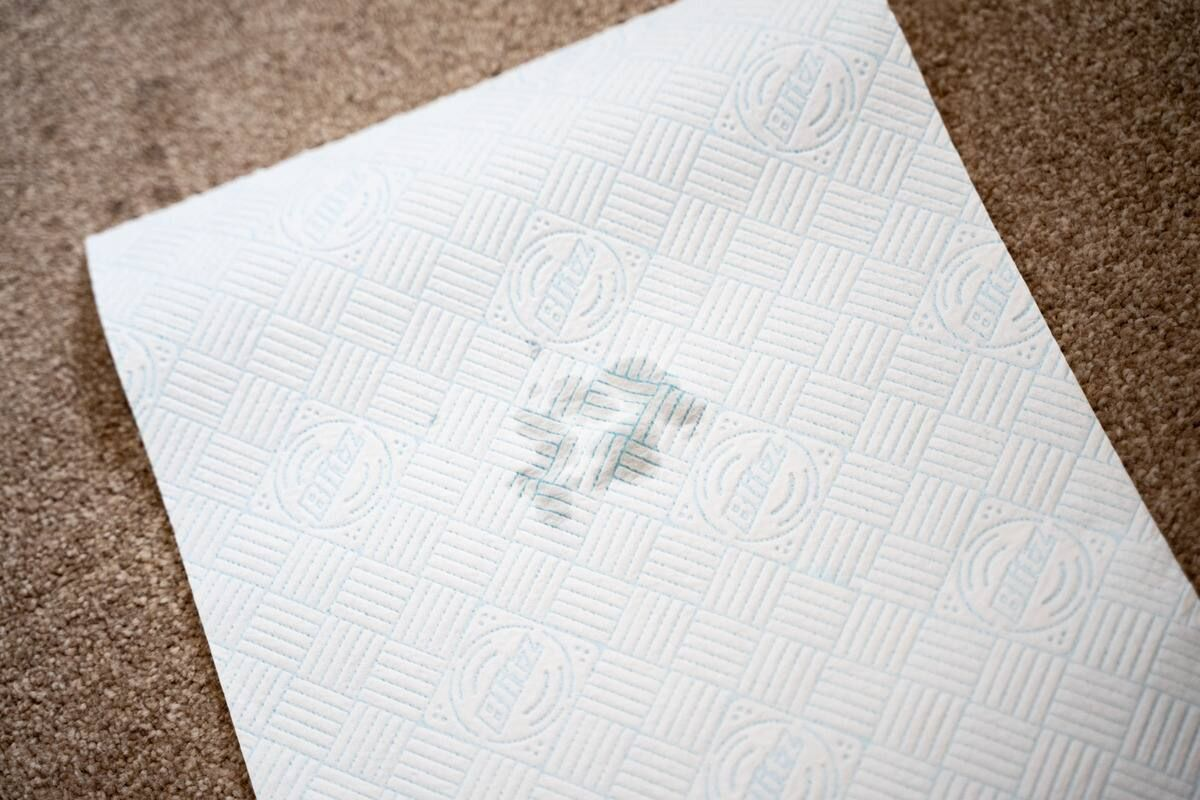 A sheet kitchen paper soaking up a stain on a carpet