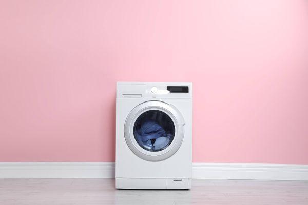 machine à laver blanche devant le mur rose