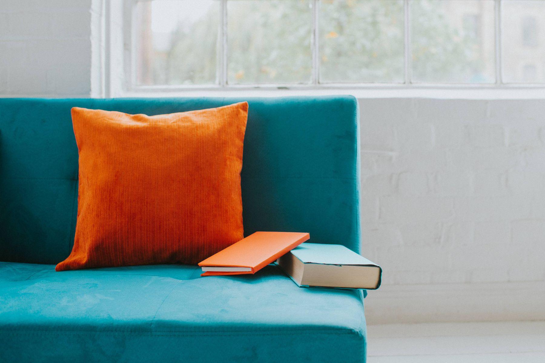sofá azul com uma almofada laranja e com dois livros, perto de parede branca com janela