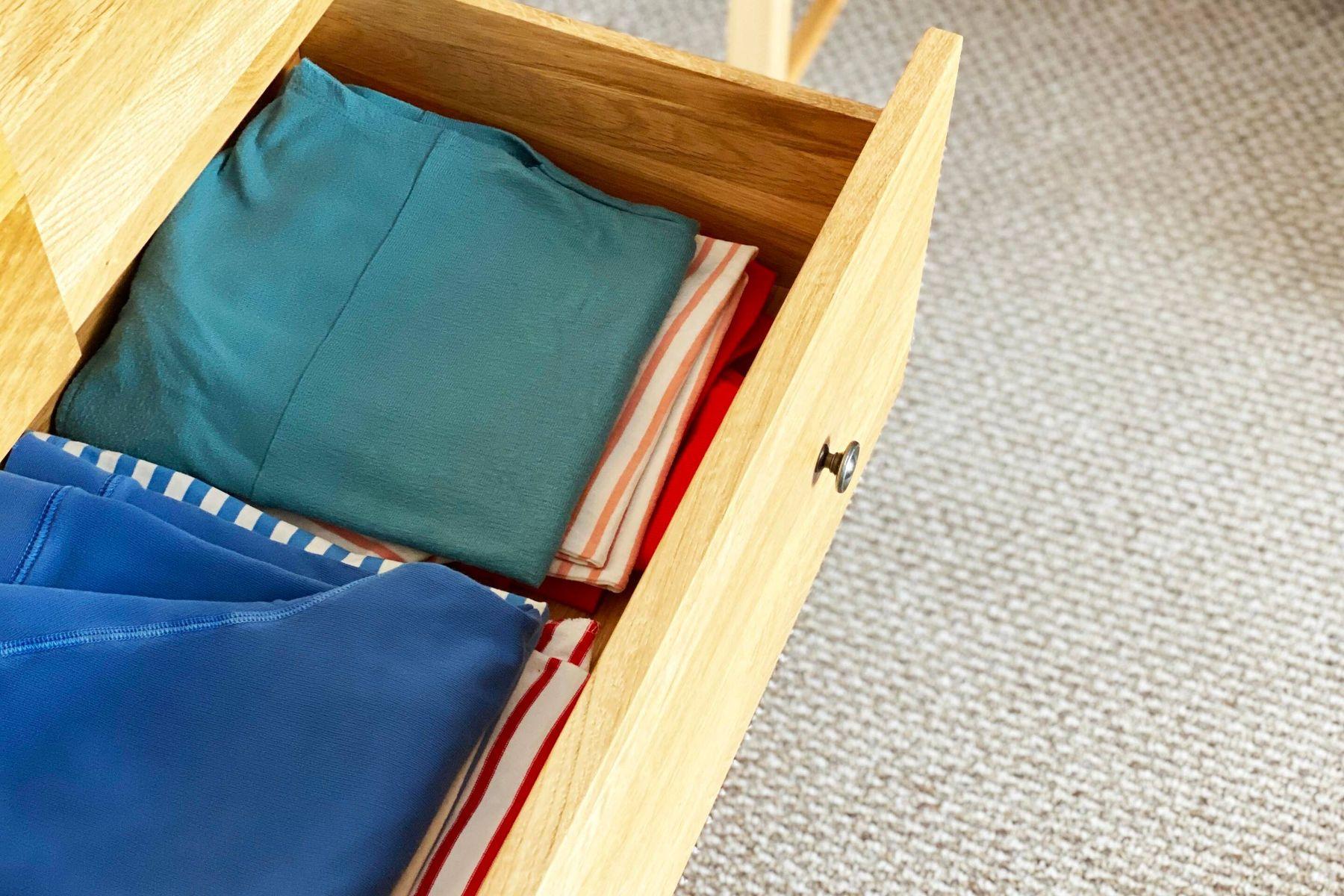 Gaveta aberta com um pilha de várias blusas de cores diferentes dentro dela