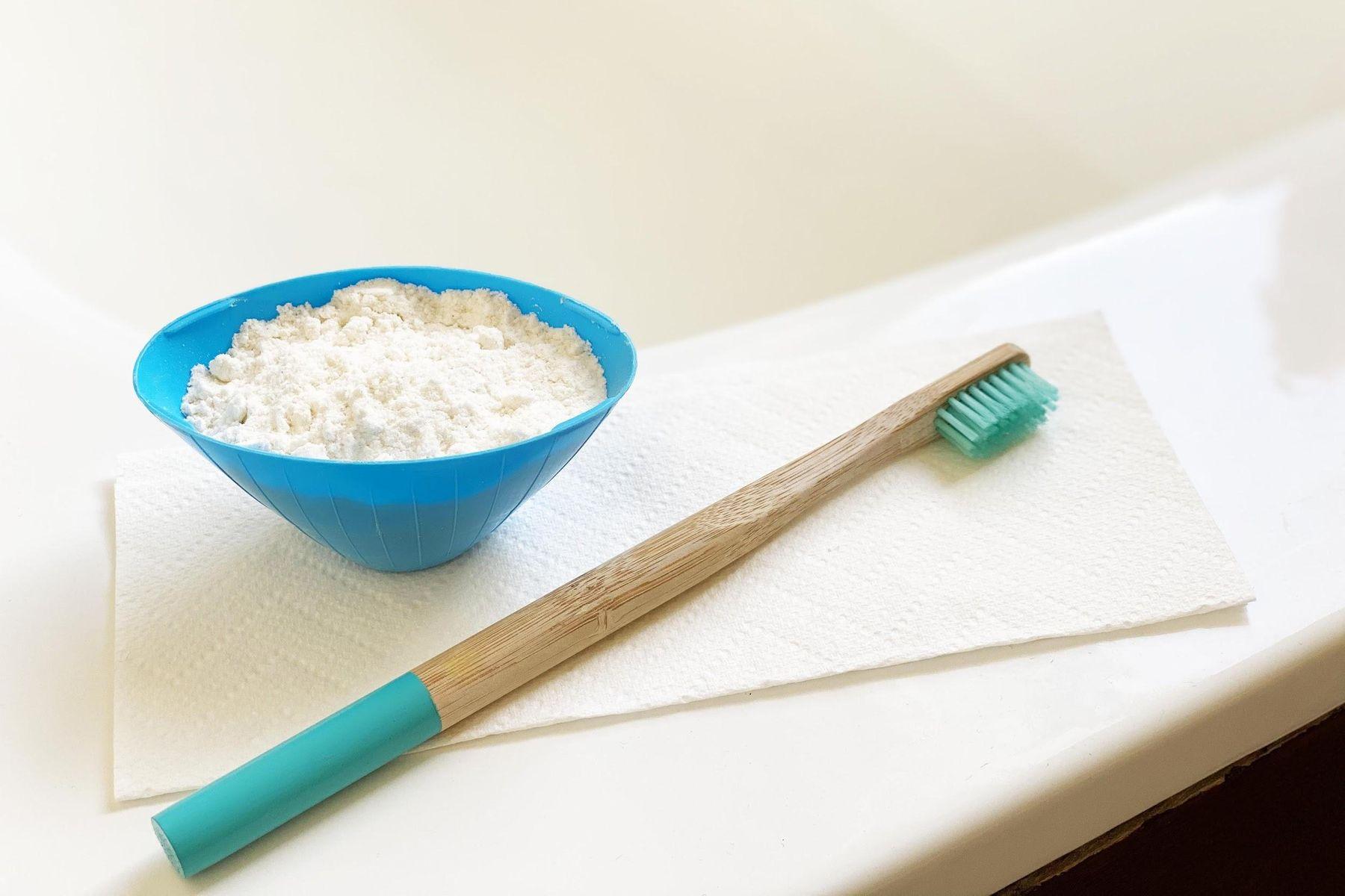 Bicarbonato para limpeza em um potinho e escova de bambu