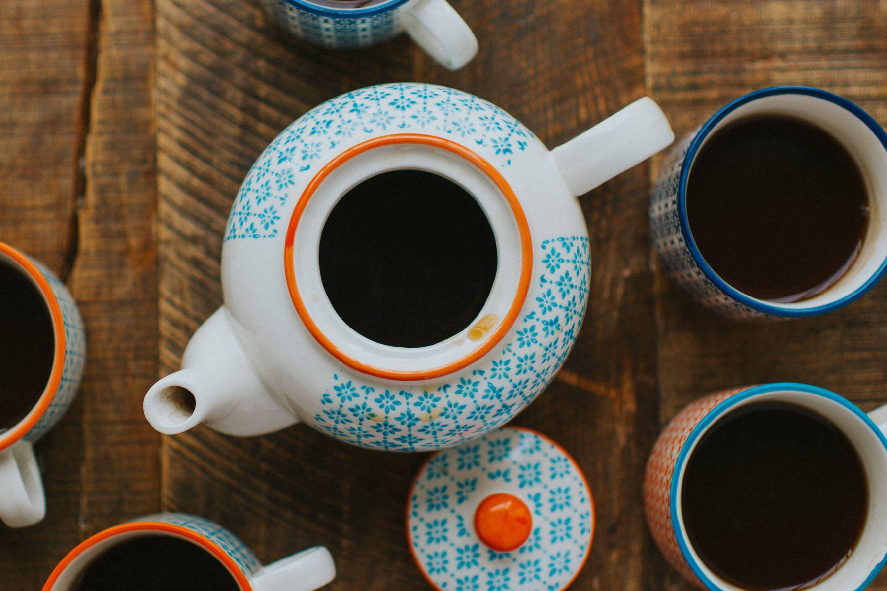 Ahşap masa üzerinde porselen demlik ve porselen çay takımı