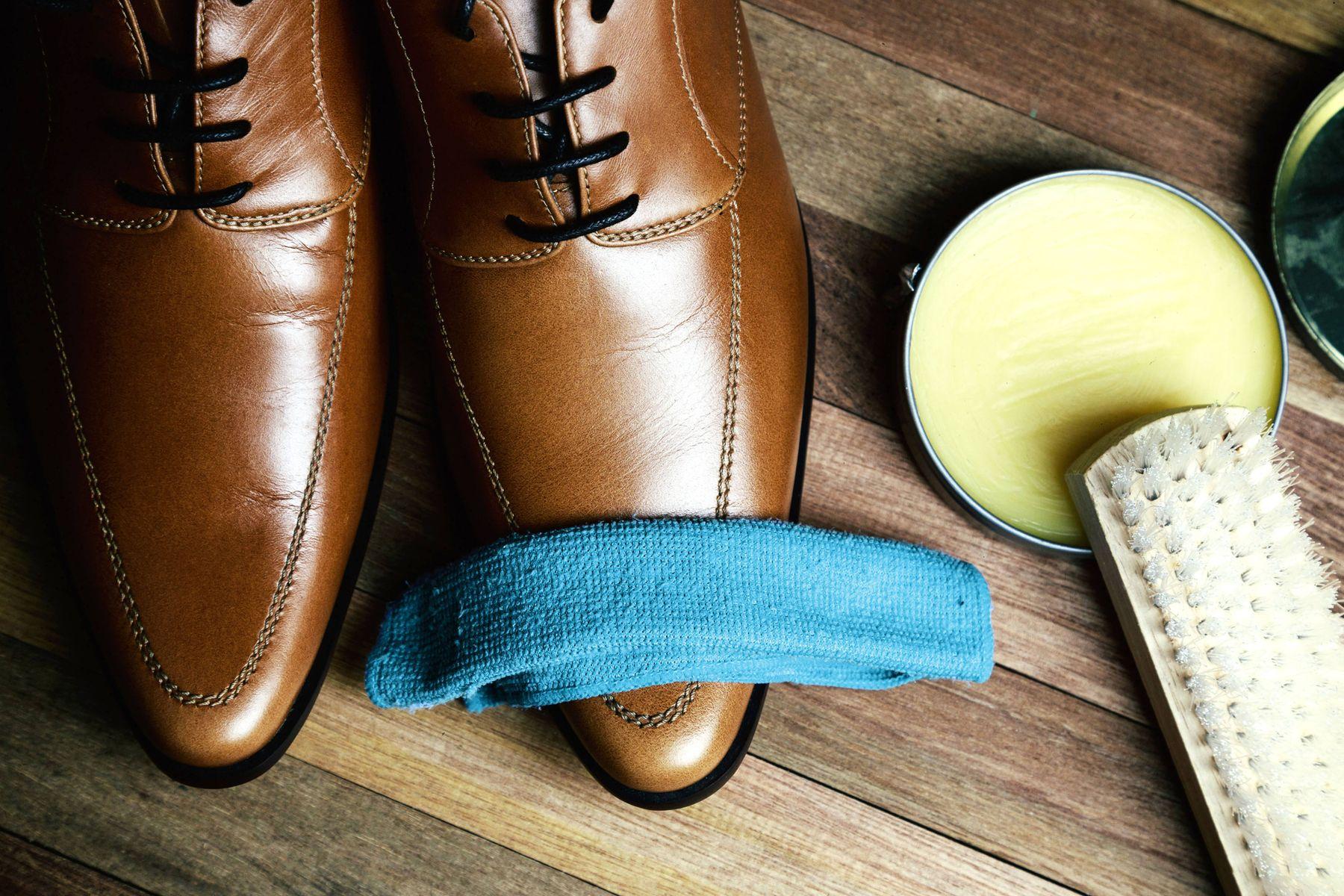 brauner Lederschuh, blaues Tuch, Pinsel und Dose Wachs
