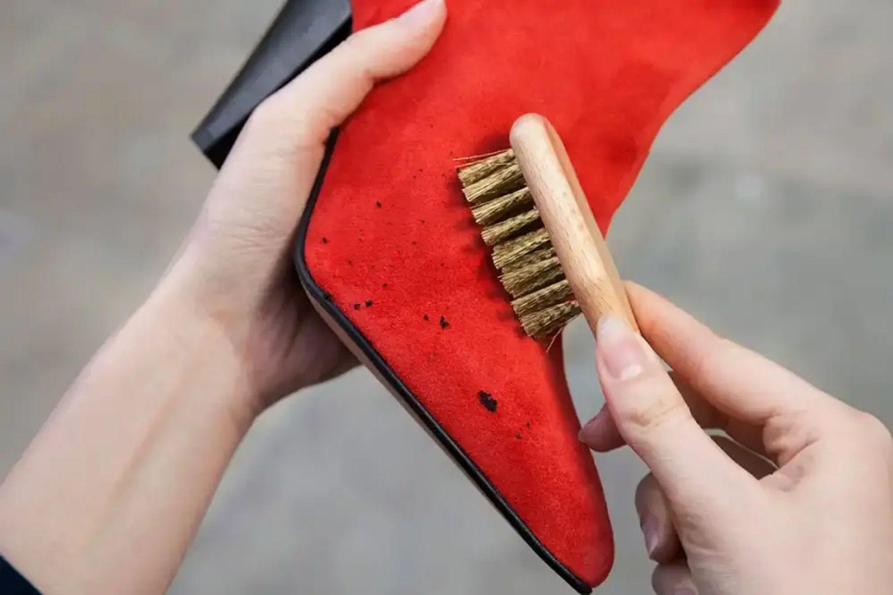 Kırmızı süet ayakkabının lekelerini fırçalayan biri