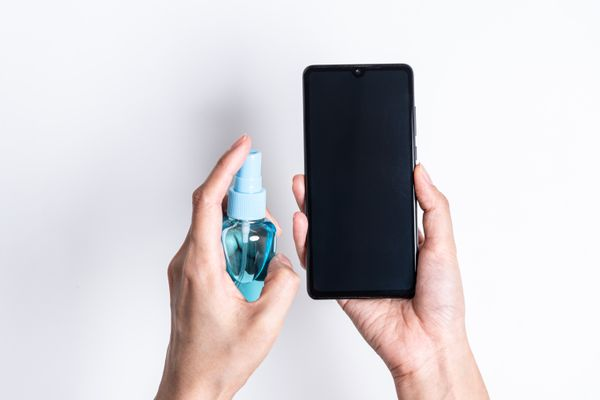 person holding a small turquoise spray bottle in one hand and a black phone in the other