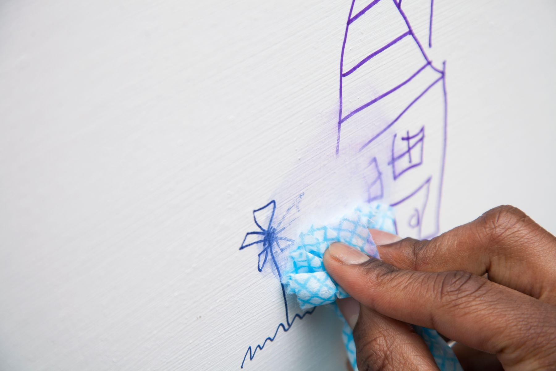 permanent marketing drawing on a wall being rubbed off with a cloth