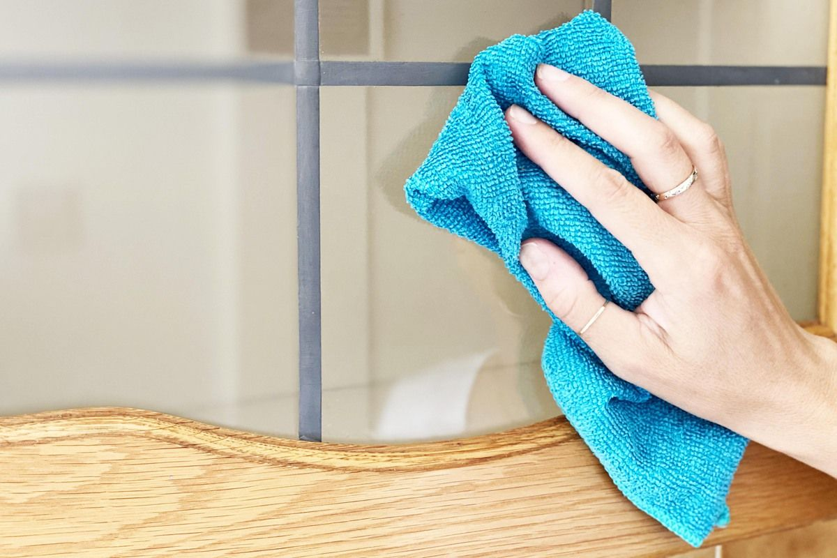 Hand using a cloth to clean wood and glass kitchen cabinet door