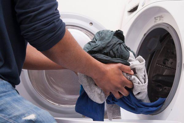 Seorang pria mencuci baju dengan mesin cuci