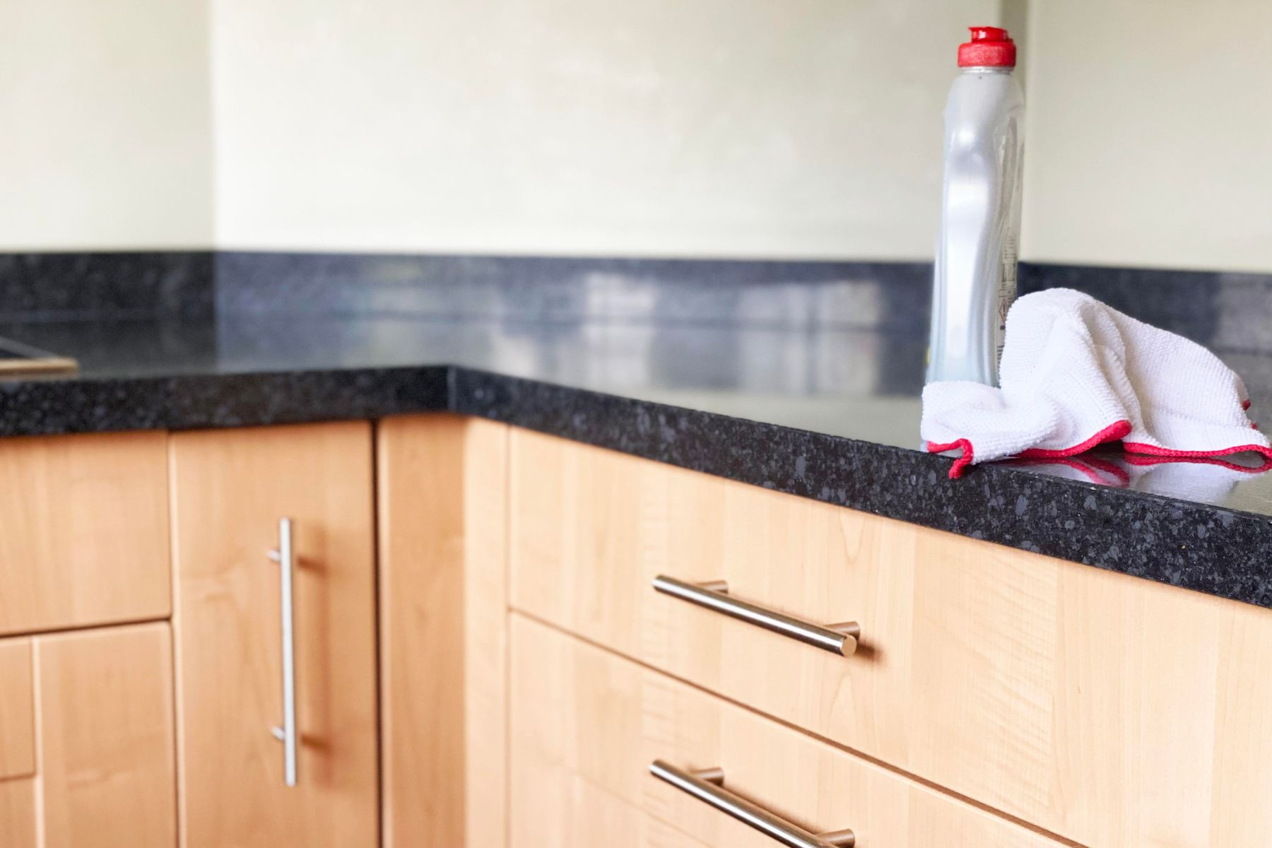 Washing up liquid and a cloth on top of a granite countertop and wooden kitchen cabinets