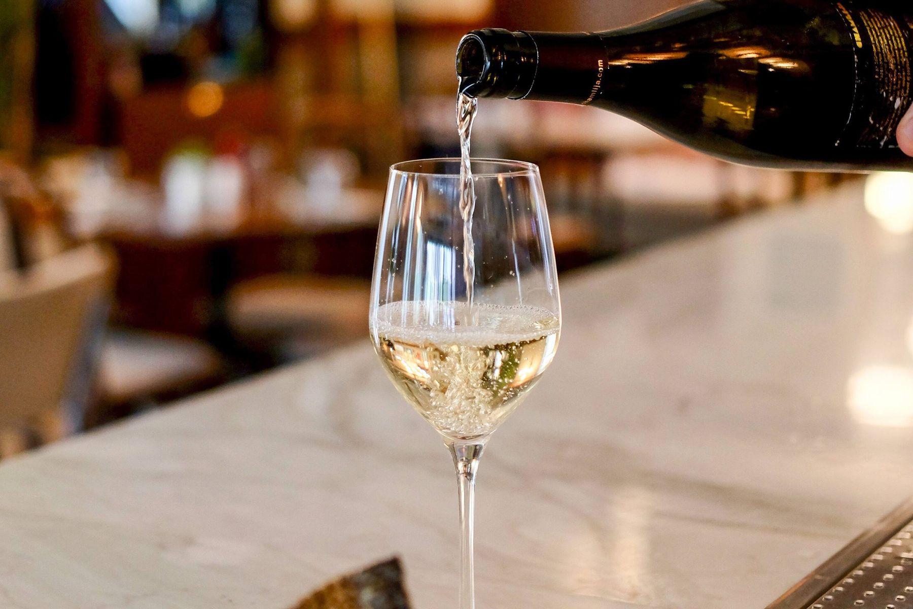 Wein wird in Weinglas eingegossen