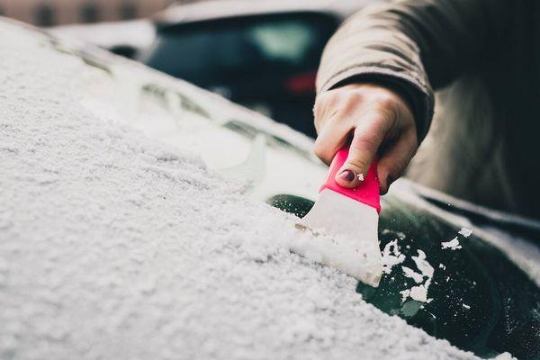 weibliche Hand mit dem Spachtel, der Eis über Autowindschutzscheibenglas entfernt