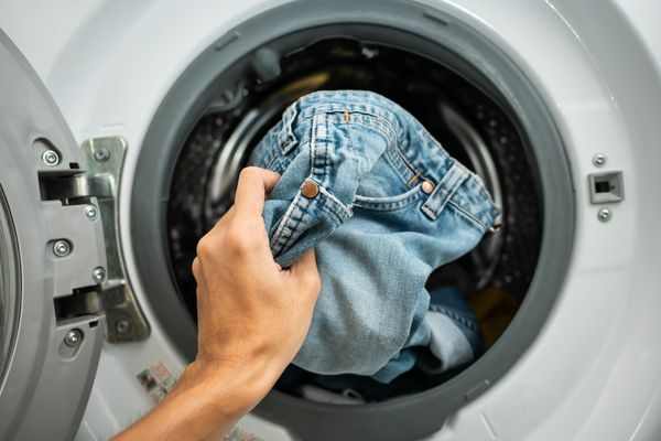 Hand putting a pair of jeans into the washing machine to demonstrate how to wash jeans