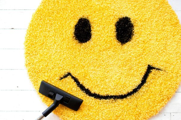 cleaning fun: smiley face rug being hoovered