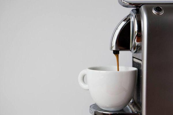 máquina cafetera vertiendo café en taza blanca