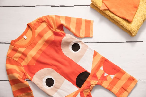 Orange baby all-in-one with a fox design