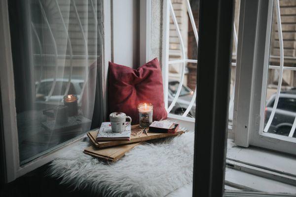Lammfell mit Kerze und Büchern am Fenster