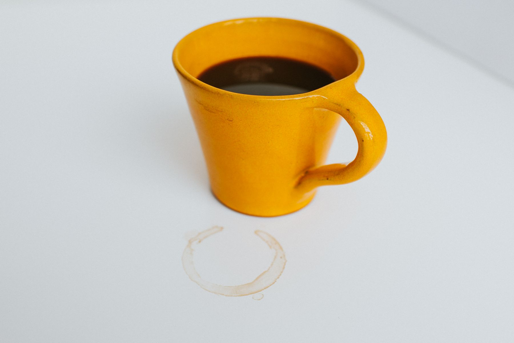 Yellow coffee cup with a stain