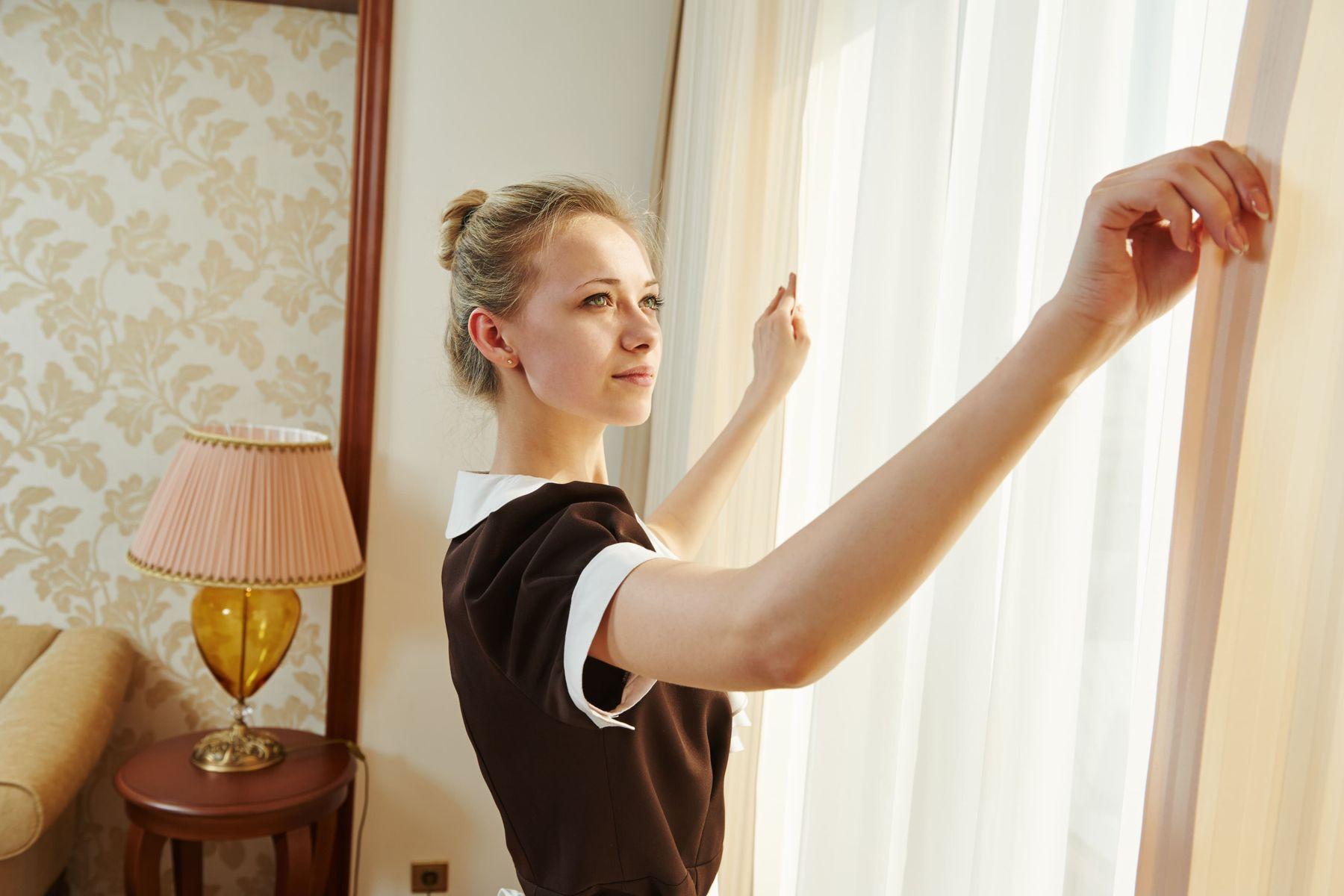 mulher abre cortina branca de quarto com abajur amarelo e papel de parede bege