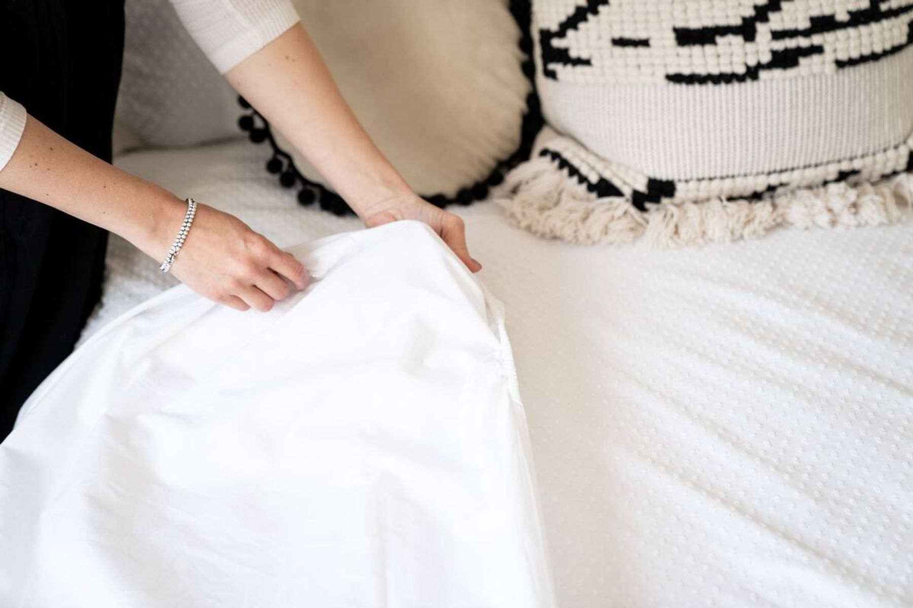 A fitted sheet being folded vertically