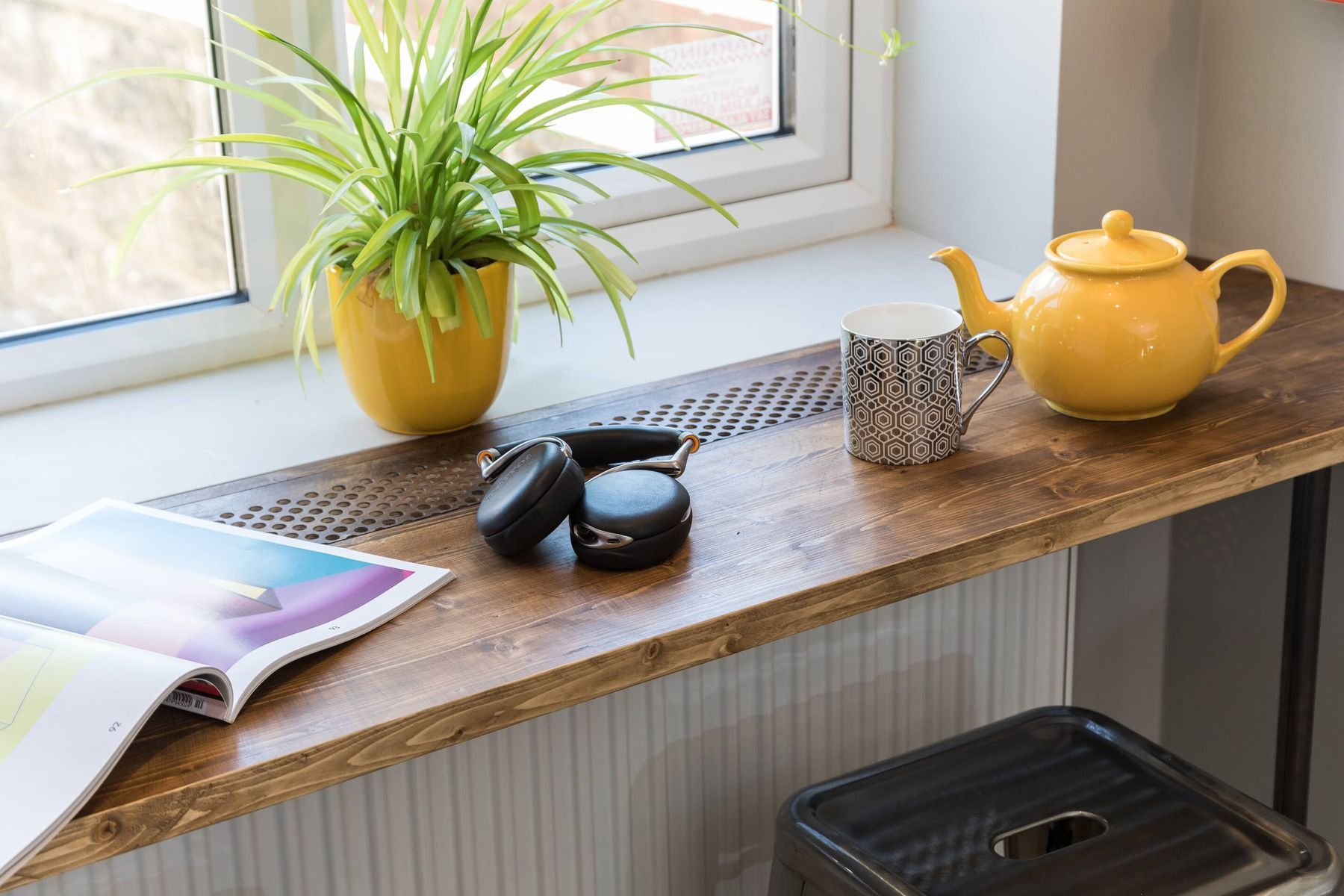 wooden sideboard under window with plant pot, yellow kettle and magazine