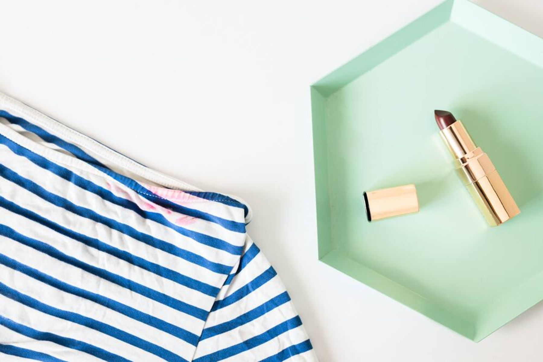 Striped top with a lipstick stain beside a tray containing an open tube of lipstick.