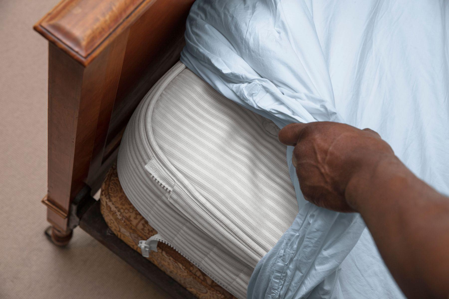 Pessoa removendo o lençol do colchão da cama de madeira